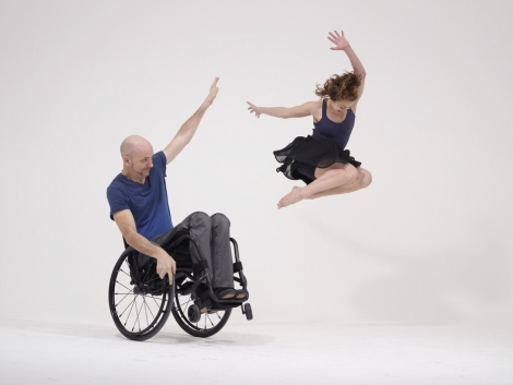 A man in a wheechair dances with a woman, who is leaping in the air