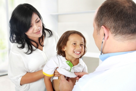 stock image of doctor performing checkup on a young boy being held by his mother
