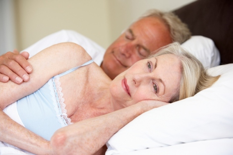stock image of couple in bed, with the man asleep and the woman awake