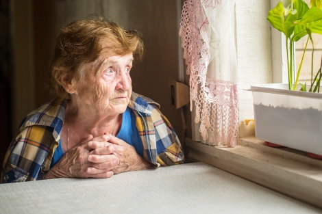 an elderly woman sits and looks out a window