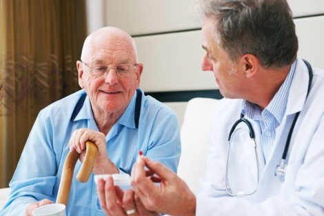 stock image of doctor discussing medication with elderly male patient