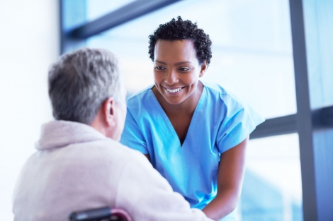 stock image of nurse smiling at an elderly male patient in a wheelchair
