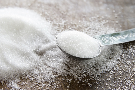 A teaspoon filled with sugar sits next to a pile of sugar