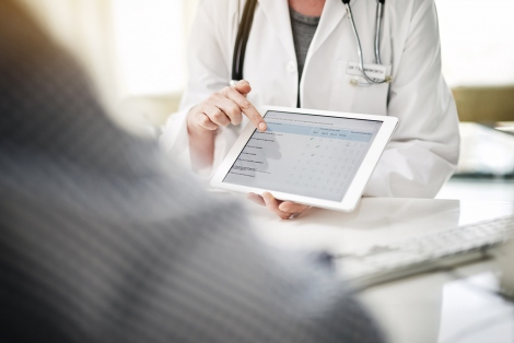 a doctor holds a tablet with a survey on it