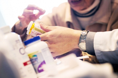 closeup of pharmacist's hands holding prescription pill bottles with patient