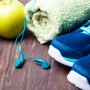 a water bottle, apple and running shoes are displayed alongside a towel and earphones