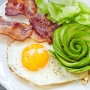 breakfast plate of fried egg, bacon, avocado