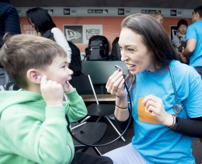 Misty Montoya teaches a child about stethoscopes at one of UCSF's hands-on learning exhibits during 2017's Bay Area Science Festival Discovery Day