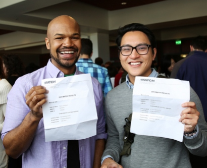 2 medical students pose for a photo with their Match Day acceptance letters