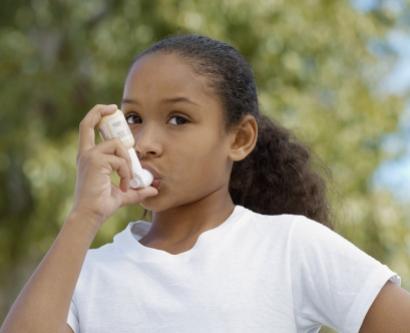 A stock image shows an African-American girl using an asthma inhaler