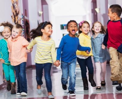 School children running down the hall holding hands.
