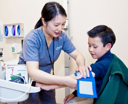 A medical assistant takes a young patient's blood pressure at UCSF Benioff Children's Hospital.
