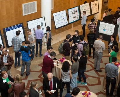 People look at posters that show the research of Disovery Fellows during the annual symposium event
