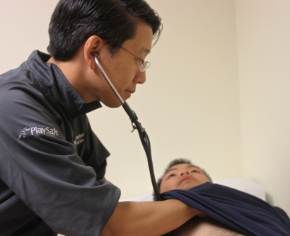 Medical physician checks heart rate of athlete