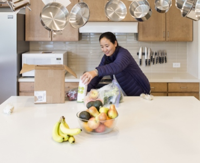 Lhamo unpacks food in a kitchen at the Family House's new home in Mission Bay
