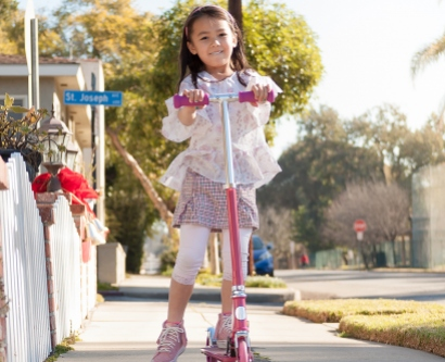 Little girl riding a scooter