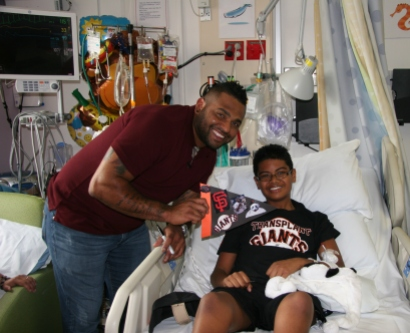 Zach Leapaga poses with Pablo Sandoval, who holds up the special flag that Zach made for the San Francisco Giants star.