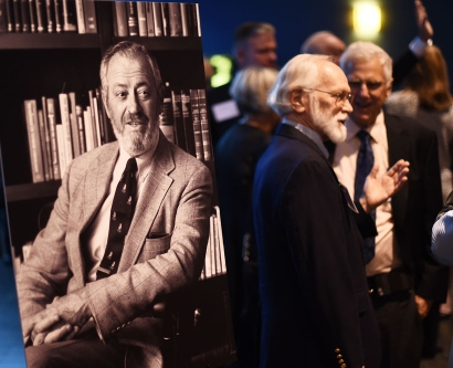 Chancellor J. Michael Bishop chats with colleagues next to a large photo of the late Chancellor Emeritus Julius Krevans