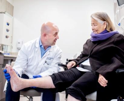 Alexander M. Reyzelman examines Diane Sammons' foot