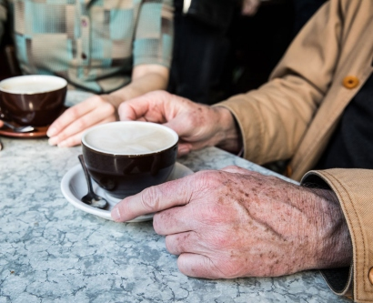 Hands of an elderly person next to coffee cup