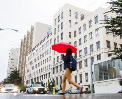 a woman crosses Parnassus Avenue in rainy weather