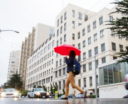 a woman crosses Parnassus Avenue in rainy weather