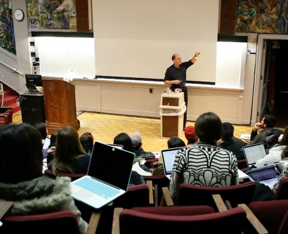 Mark Ryder doing a magic trick in a large lecture hall