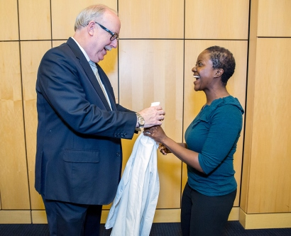 UCSF School of Nursing Dean David Vlahov hands a white coat to a new student in a white coat ceremony