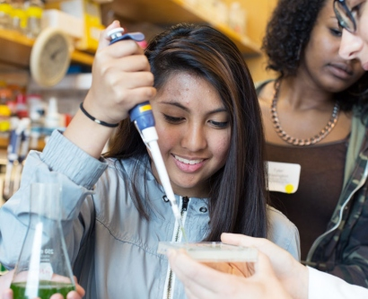 A high school student tries out a pipette in the lab of UCSF's Peter Walter during STEM Career Day 2015