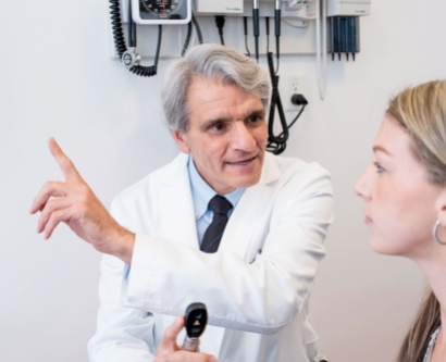 Dr. Stephen Hauser, examining a patient, gestures for her to look straight ahead