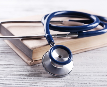A stock image shows a stethoscope sitting atop a book