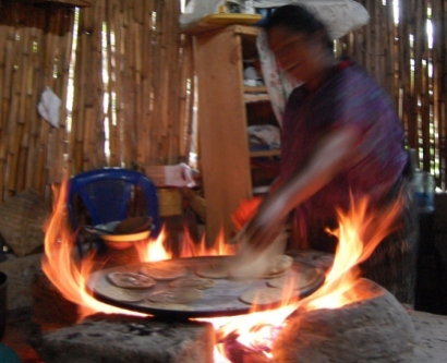 A woman cooks tortillas on a wood-fired three-stone stove in Guatemala.