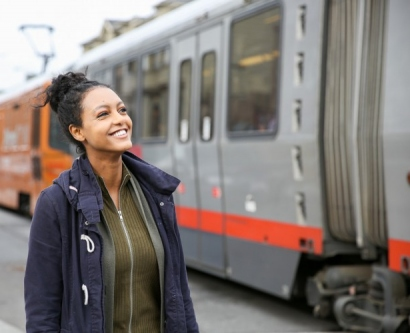 a woman stands by a Muni train