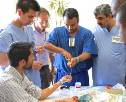 Samir Soomro, MD, a trauma surgeon from Pakistan, right, observes his colleagues  draw blood using a makeshift contraption during the UCSF trauma summit.