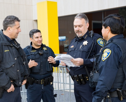 UCSF Police Department Chief Mike Denson talks with three other officers