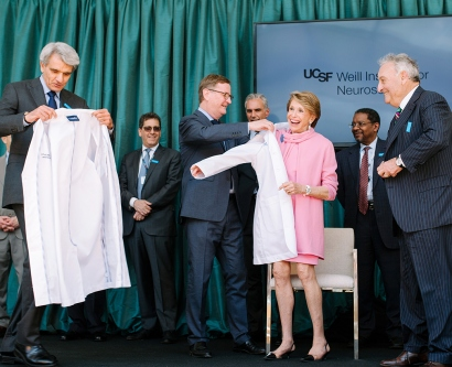 Stephen Hauser and UCSF Chancellor Sam Hawgood present Joan and Sandy Weill with white physicians' coats