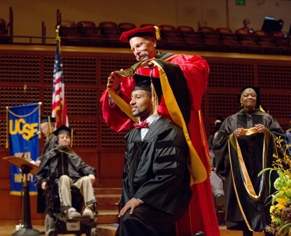 School of Pharmacy Dean B. Joseph Guglielmo places a doctoral hood over the head of Henock Woldu, signifying his completion of the PharmD program,