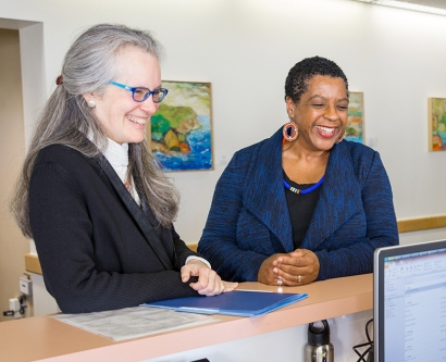 Nancy Milliken, Judy Young and Nicole Galvin talk at the front desk of the UCSF National Center of Excellence in Women's Health.