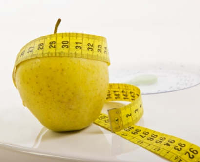 Stock image of apple and measuring tape on a scale