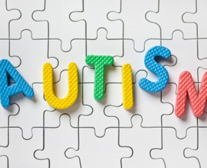 "Letters spelling ""autism"" over puzzle pieces"
