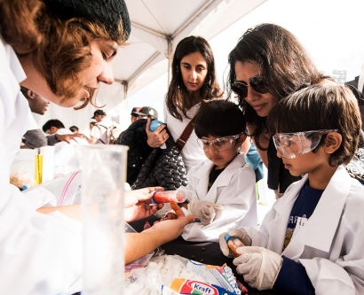 Children in goggles and lab coats help run an experiment involving marshmallows and fluids