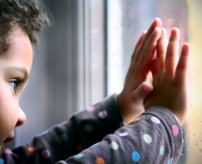Stock image of boy holding his hands against a window