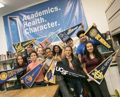 Teens from the Boys and Girls Club of America hold pennants with the names of the nine UC schools