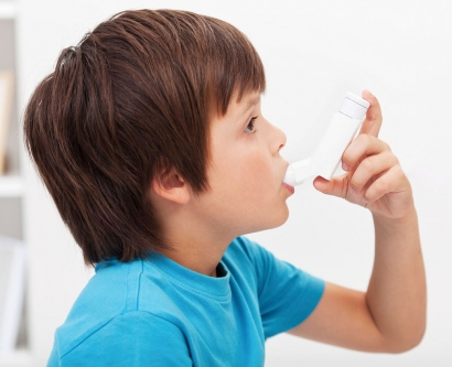 A stock image shows a young boy using an asthma inhaler