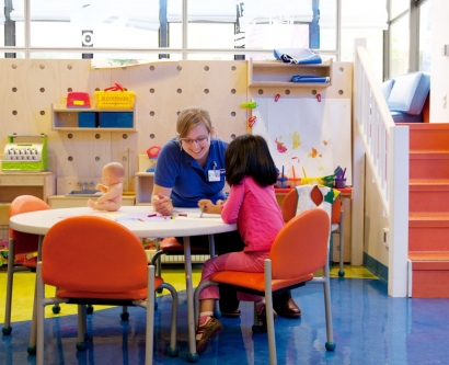 A volunteer plays with a young patient in the playroom of UCSF Benioff Children's Hospital.