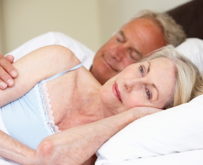 stock image of a couple lying in bed, with the man asleep and the woman awake