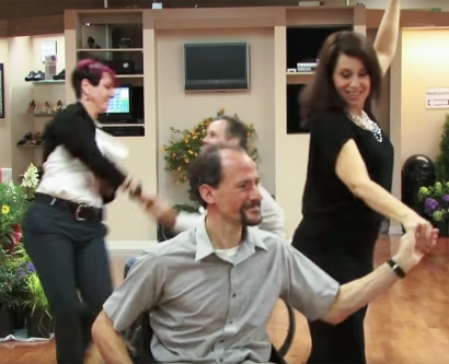 two men in wheelchairs dance with women