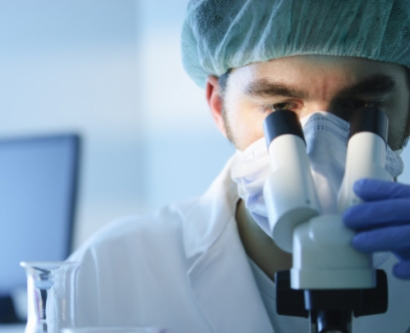 Stock image of researcher looking through a microscope