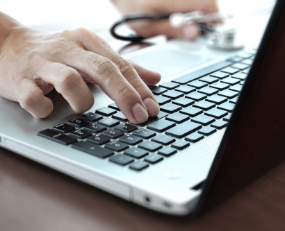 close-up of doctor's hand on a computer keyboard