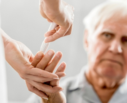 Stock photo of elderly man having his blood sugar checked